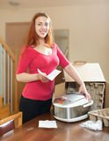 Young red haired housewife unpacking new multicooker in living r Royalty Free Stock Photo