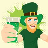 Man St Patrick Day. Young red haired man with beard celebrating St.Patrick`s day holding glass of green beer Royalty Free Stock Image
