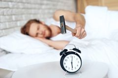 Young red haired man hammers alarm clock. stock photos
