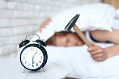 Young red haired man hammers alarm clock. royalty free stock images