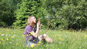 Young red-haired man sitting in the grass and blowing soap bubbles stock video