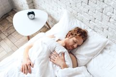 Young red haired man is sleeping in bed stock photos