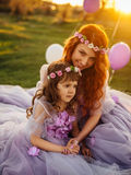 Young red-haired mother with her daughter resting on nature in the sun Royalty Free Stock Photography