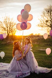 Young red-haired mother with her daughter resting on nature in the sun Stock Photos