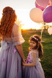 Young red-haired mother with her daughter resting on nature in the sun Stock Image