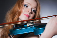 young red-haired musician with blue violin Royalty Free Stock Photo