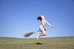 Young red-haired witch on broom flying over green Stock Photos