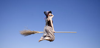 Young red-haired witch on broom flying in the sky Stock Photo
