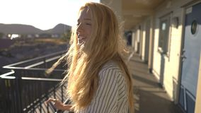 Young red-haired woman admiring the sea views on the hotel terrace on the coast in Northern Europe. Slow motion stock footage