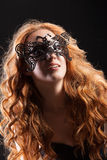 Young Red- Haired Woman In A Black Mask Stock Photo