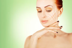Young red haired woman closeup with surgery lines, green gradien Royalty Free Stock Images