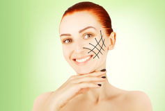 Young red haired woman closeup with surgery lines, green gradien Stock Image