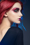 Young red-haired woman with colorful make up. Isolated studio portrait Royalty Free Stock Photo