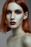 Young red-haired woman with colorful make up. Isolated studio portrait Stock Images