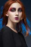 Young red-haired woman with colorful make up. Studio portrait Royalty Free Stock Photos