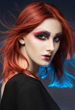 Young red-haired woman with colorful make up. Studio portrait Royalty Free Stock Image