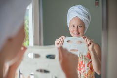 Young red-haired woman doing facial mask sheet. Beauty and Skin Care Concept stock photos