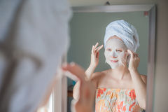 Young red-haired woman doing facial mask sheet. Beauty and Skin Care Concept stock photo