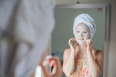 Young red-haired woman doing facial mask sheet. Beauty and Skin Care Concept royalty free stock photos