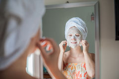 Young red-haired woman doing facial mask sheet. Beauty and Skin Care Concept royalty free stock photo