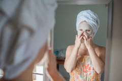 Young red-haired woman doing facial mask sheet. Beauty and Skin Care Concept stock images