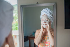 Young red-haired woman doing facial mask sheet. Beauty and Skin Care Concept royalty free stock photography
