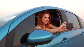 Young red-haired woman doing selfie smartphone in her car stock video footage