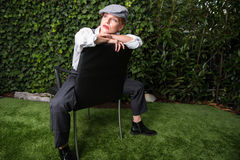 Young red-haired woman dressed as a man in the Twenties year sty. Le on a chair Royalty Free Stock Photography