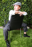 Young red-haired woman dressed as a man in the Twenties year sty. Le on a chair Royalty Free Stock Images