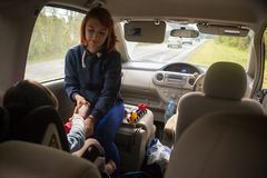 Woman dressing a young child. A young red-haired woman dressing a young child in a car seat in the car. Car trip with a child in the mountains Stock Photos