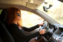 Young red-haired woman driving car Royalty Free Stock Image