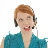 Young red haired woman with head set looking surprised Royalty Free Stock Photo