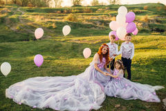Young red-haired woman with her children in smart clothes playing with balloons in the park Stock Photography