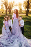 Young red-haired woman with her children in smart clothes standing in the park Royalty Free Stock Photography