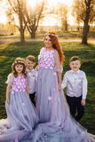 Young red-haired woman with her children in smart clothes standing in the park Stock Images