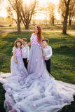 Young red-haired woman with her children in smart clothes standing in the park Stock Image