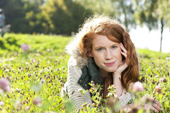 Young red haired woman lying in the grass Royalty Free Stock Image