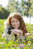 Young red haired woman lying in the grass Stock Photo