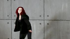 Ginger woman doing hip-hop near by wall. Young red-haired woman performs in black clothes near wall stock video