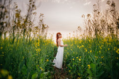 Young red-haired woman in a rapeseed field. Young beautiful red-haired woman in a blooming rapeseed field at sunset Royalty Free Stock Photos