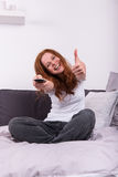 Young red-haired woman with the remote control in her hand watch Stock Photography