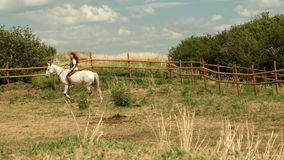 A young red-haired woman rides a horse.