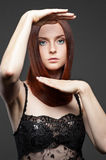 Young red-haired woman with rised hands Stock Images
