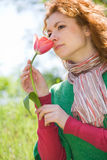 Young red-haired woman smelling red tulip Royalty Free Stock Images
