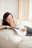 Young red-haired woman studying on the sofa Royalty Free Stock Images