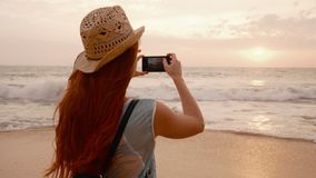 Young woman tourist taking pictures of the sunset by the ocean. Young red-haired woman tourist taking pictures using a smartphone sunset on the ocean beach, slow stock video