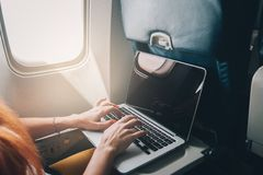 Woman uses a laptop while on a plane. Young red-haired woman uses laptop while flying on airplane near window, close-up Royalty Free Stock Photography