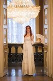 Young red haired woman in vintage 18 centuries dresses use fan in luxury ballroom. Telephoto royalty free stock image