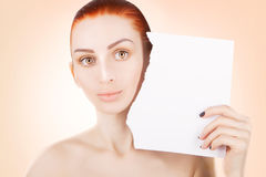 Young red haired woman with white paper, pink background. Young red haired woman with white paper, space for text Royalty Free Stock Photo