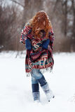Young red-haired woman in the winter forest. She is dressed in an ethnic scarf Stock Images